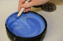 Mélange à la cuillère du plâtre liquide avec un pigment bleu