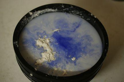 Un bol contient de l'eau, du plâtre et du pigment bleu